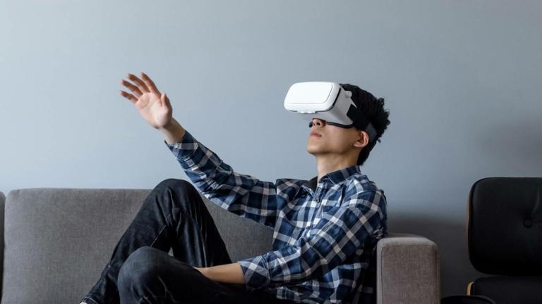 Student im Profil mit VR-Brille auf Sofa