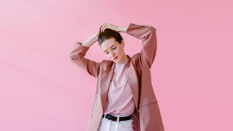 Frau in rosa Blazer vor Hintergrund in Pink