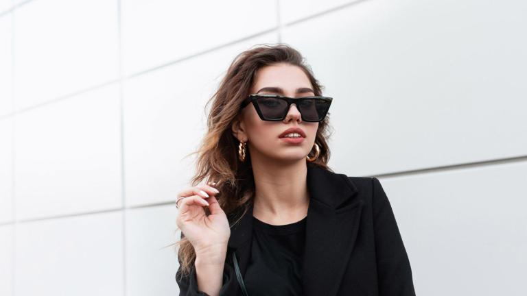Junge Frau in Scchwarz mit extravaganter Sonnenbrille